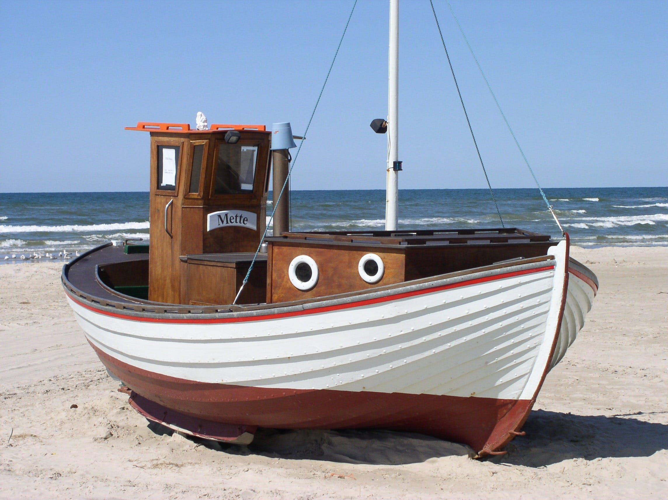 White and Brown Speedboat on White Sand Beside Ocean during Daytime