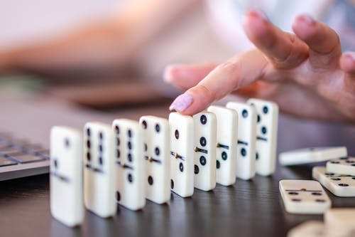 Person Holding White Dice on Black Wooden Table