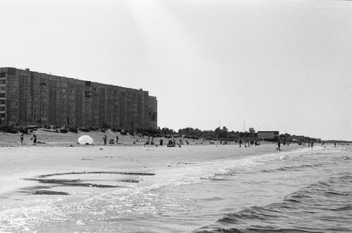 Grayscale Photo of People on the Beach