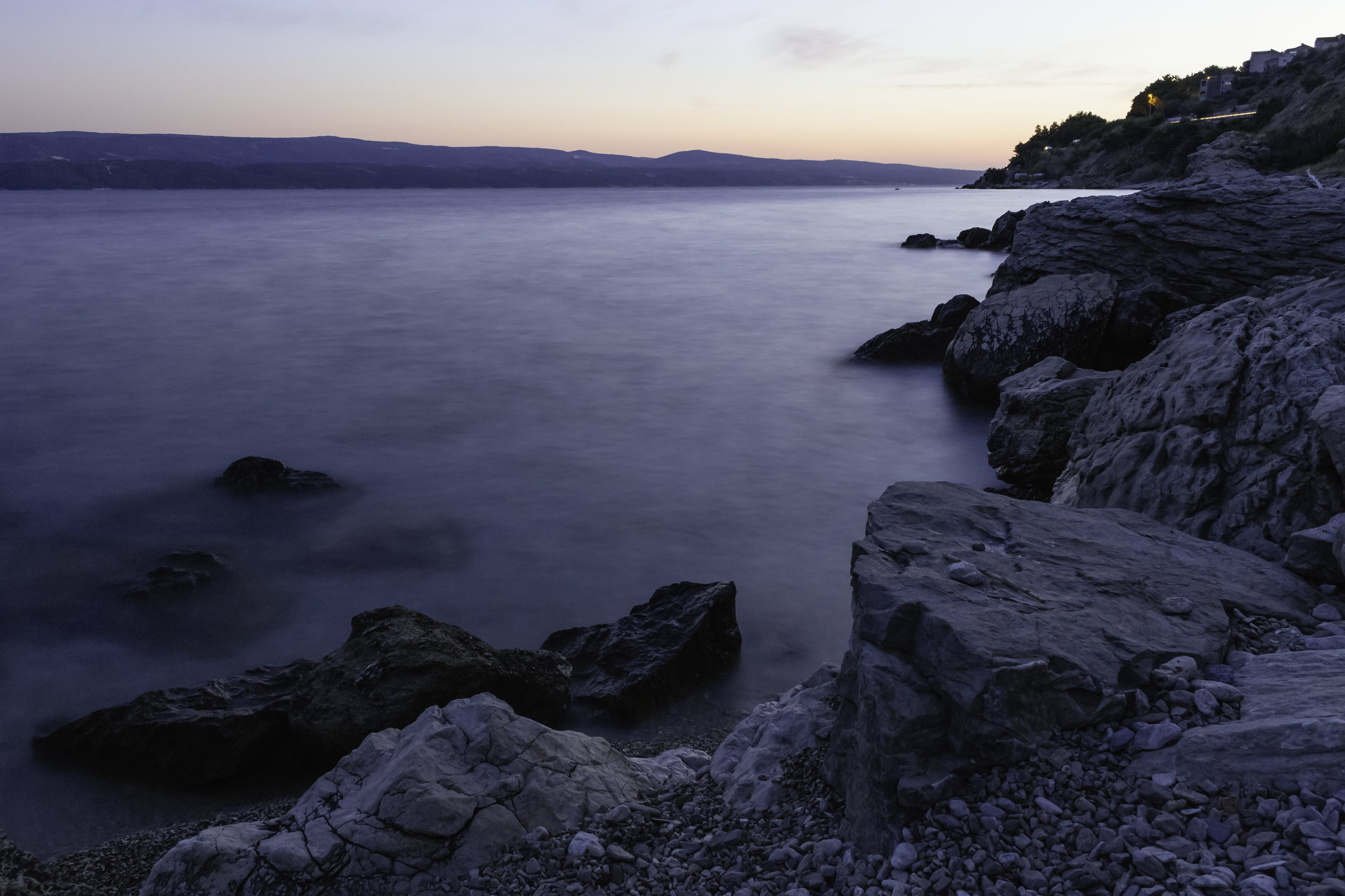 Photo of Calm Body of Water Beside Rock Formations