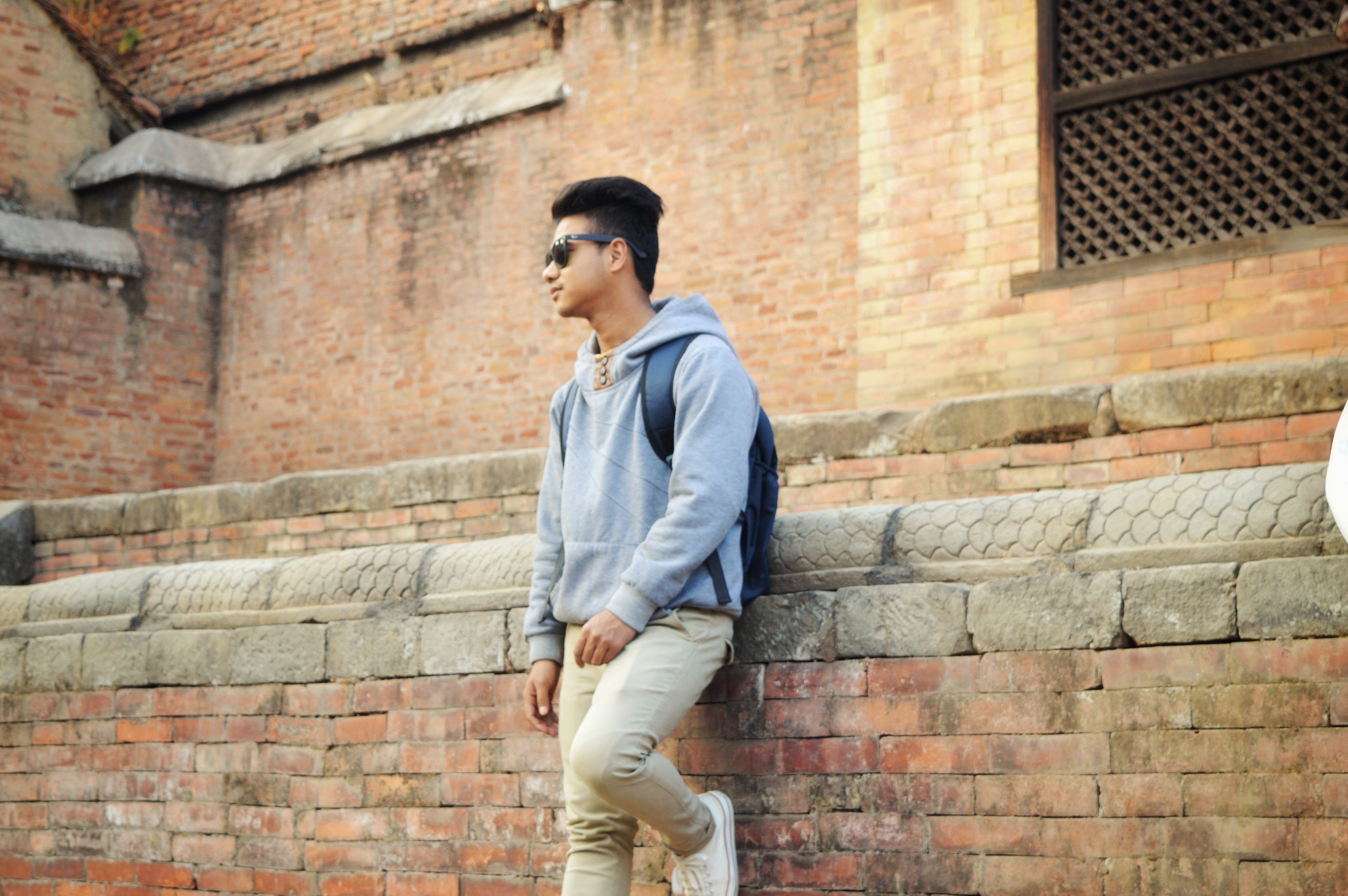 Man in Heather-grey Pullover Hoodie and Beige Pants Standing Near Brick Wall