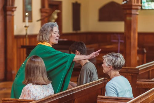 An Elderly Woman Giving Blessing To A Churchgoer
