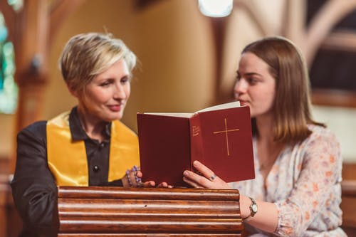 Women Looking at an Opened Bible