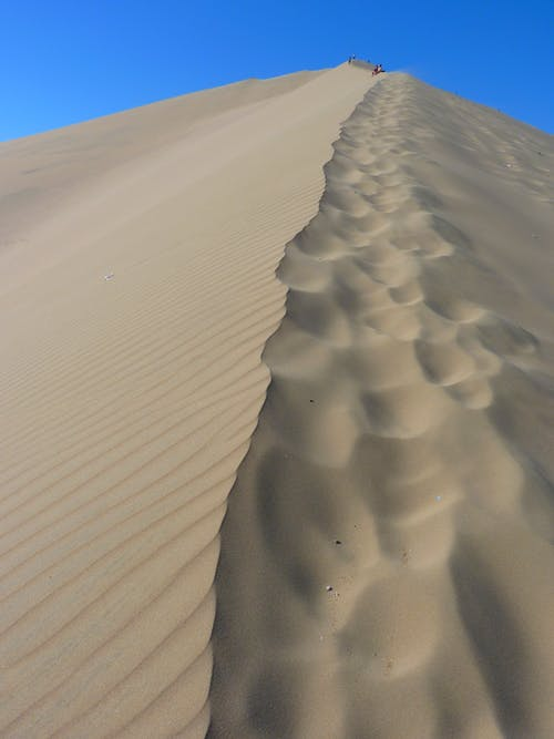 Brown Sand Dunes Under Blue Sky