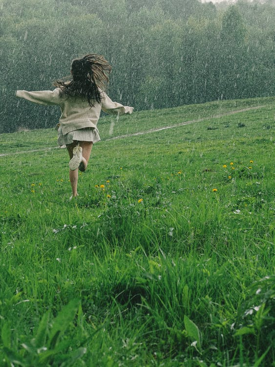 A Person Running in a Grass Field While Raining