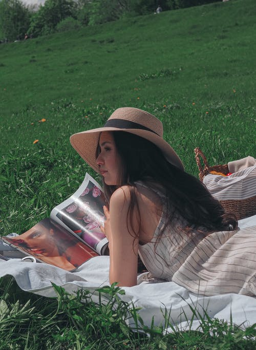 A Woman Holding a Magazine While in a Prone Position