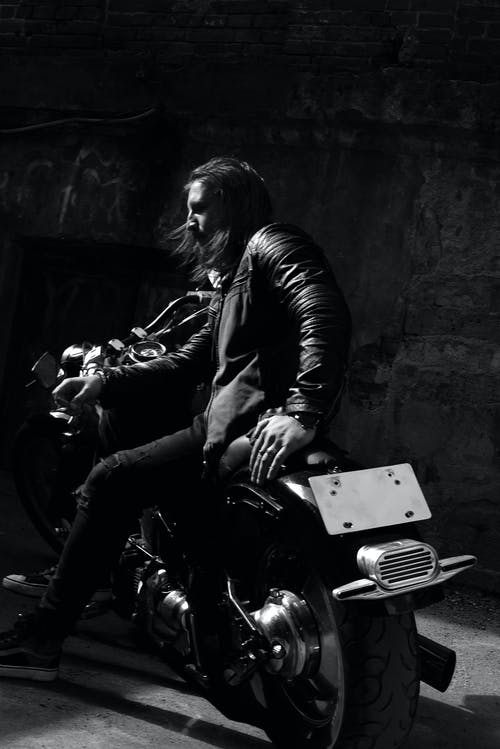 Man in Black Leather Jacket and Black Pants Sitting on Motorcycle