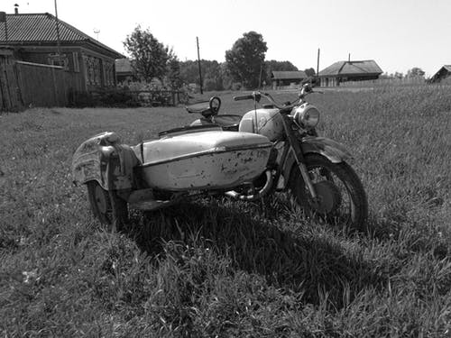 Grayscale Photo of Vintage Motorcycle with Sidecar on Grass