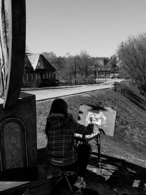 Grayscale Photo of a Person Doing an Artwork
