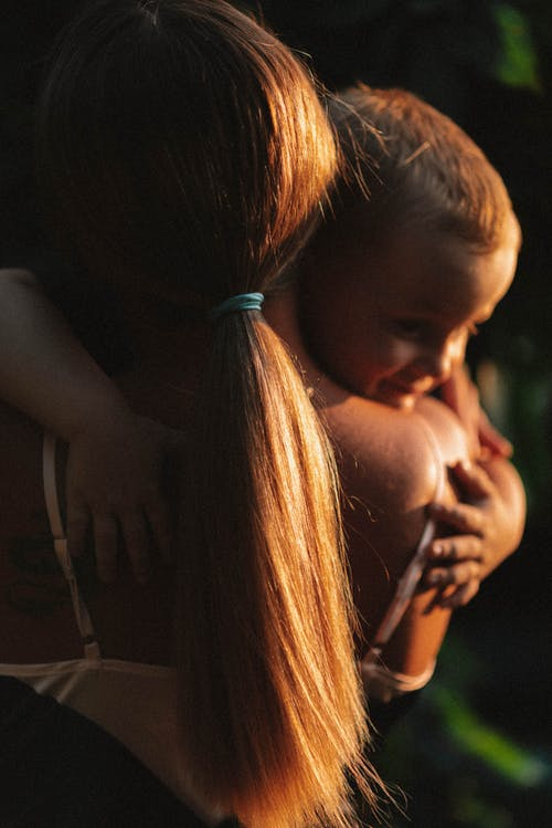 Close-Up Photo of a Mother and Child Hugging Each Other