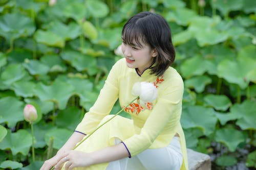 Shallow Focus Photo of a Smiling Woman in Yellow Ao Dai Holding a White Flower