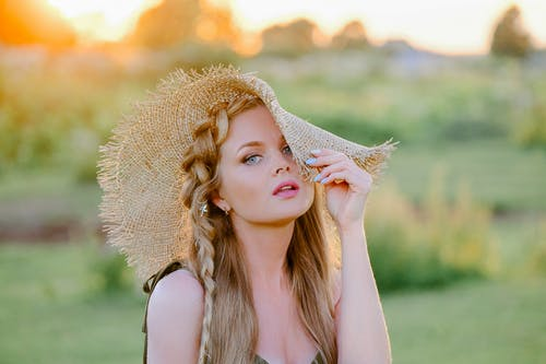 Selective Focus Photo of a Beautiful Woman Touching Her Straw Hat