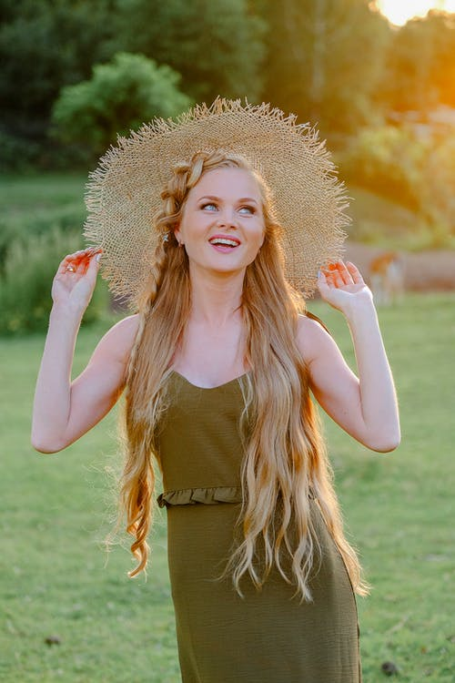 Photo of a Blonde Woman with Long Hair Touching Her Straw Hat