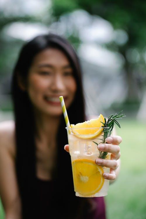 拿著黃色液體的透明玻璃杯的女孩