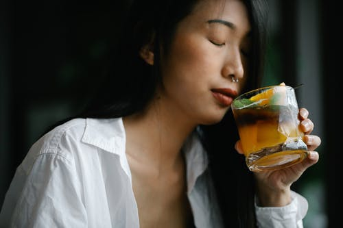 Woman in White Dress Shirt Holding An Alcoholic Beverage