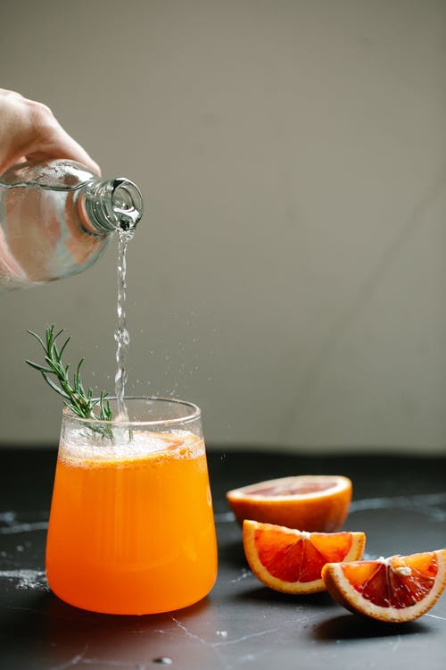 Person Pouring Alcohol On Fresh Fruit Juice Drink