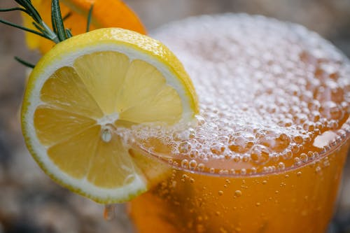 Clear Drinking Glass With Orange Juice and Lemon Slice