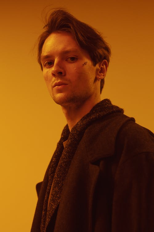 Man in Brown Coat Standing Near Yellow Wall