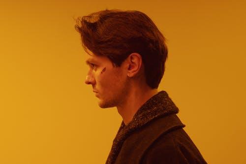 Man in Brown Coat Looking Down