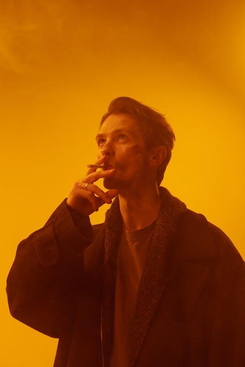 Man in Black Coat Smoking Cigarette