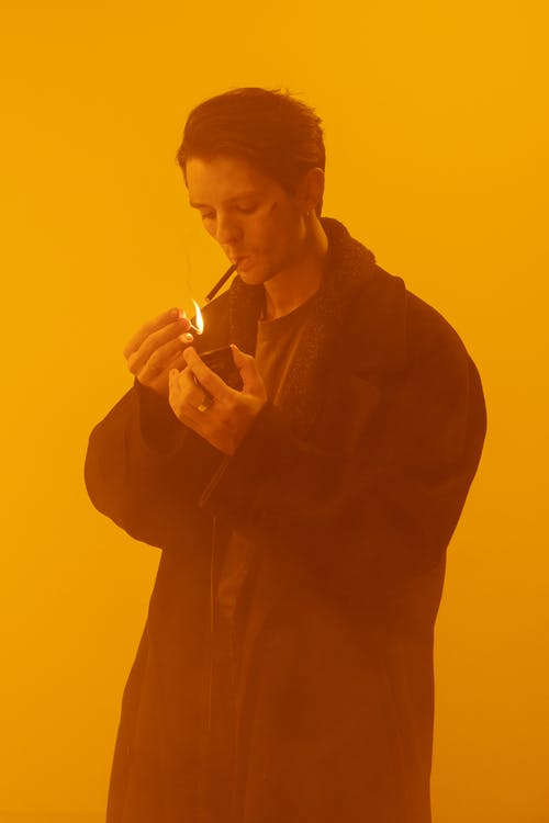 Man in Black Robe Smoking Cigarette