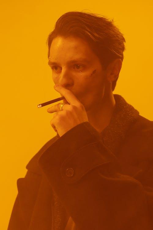 Woman in Brown Coat Smoking Cigarette