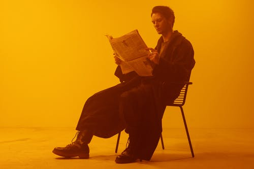 Man in Black Jacket Sitting on Chair Reading Book