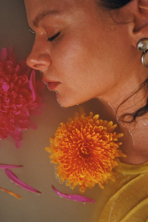 Woman With Yellow and Red Flower on Her Ear