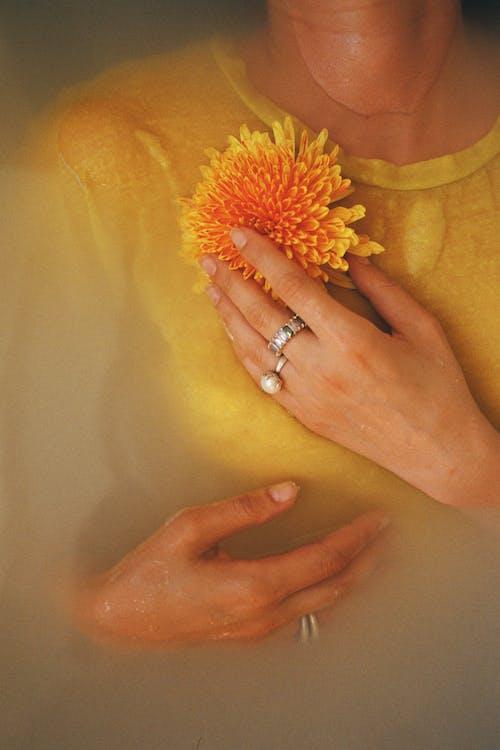Woman in Yellow Crew Neck Shirt Holding Orange Flower