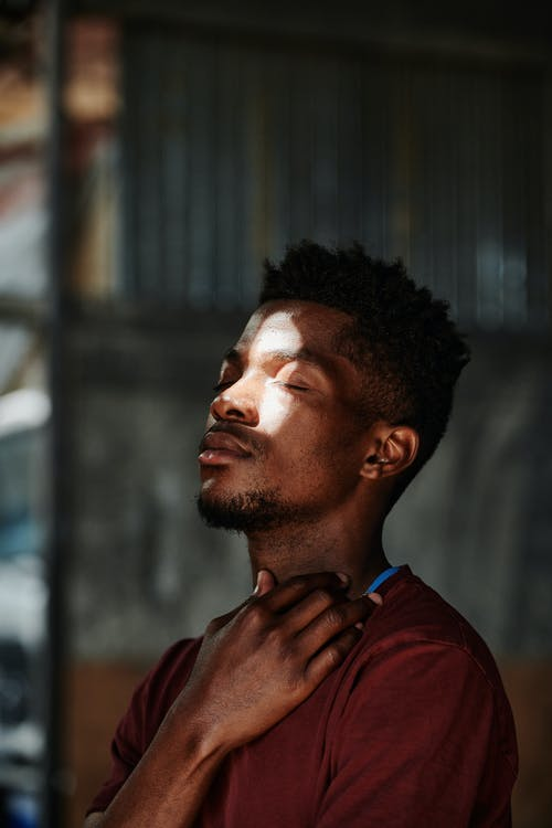 Selective Focus Photo of a Man in a Red Shirt with Sunlight on His Face