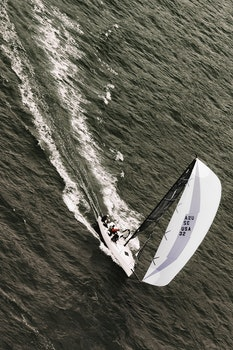 People Riding on White Sailboat on Body of Water