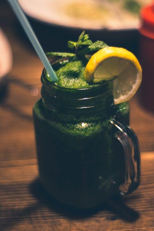 녹색 주스와 슬라이스 감귤류 토핑이 들어간 투명 유리 메이슨 항아리 머그잔의 클로즈업 사진