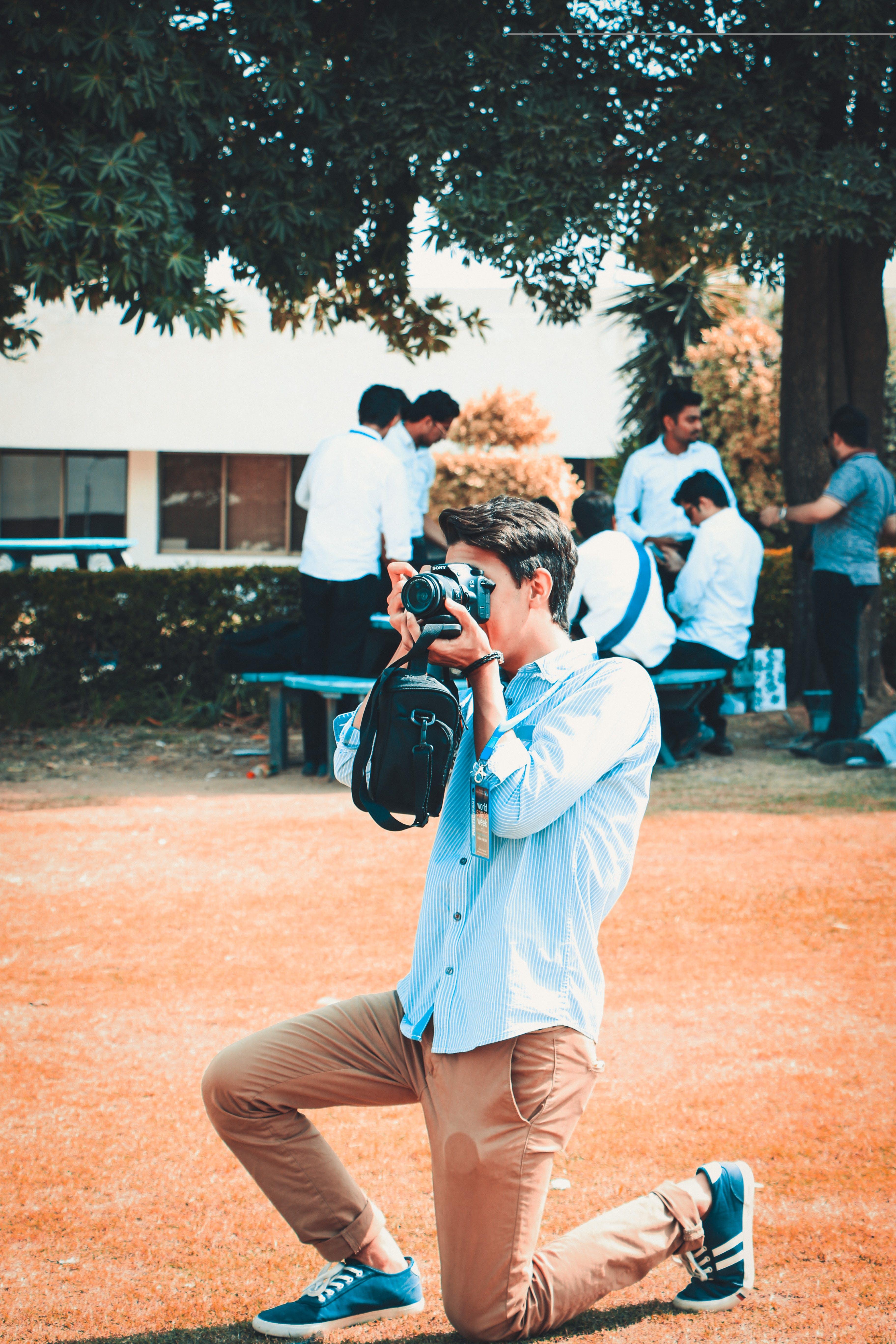 Man Holding a Black Dslr Camera