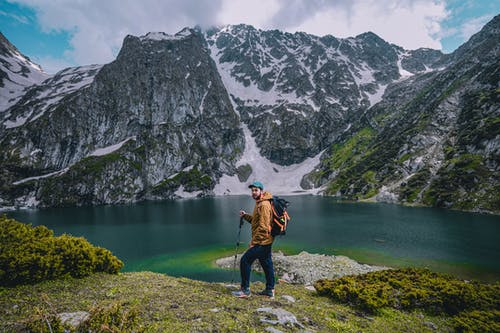 An Adventurous Man Standing Across the Lake and Mountain