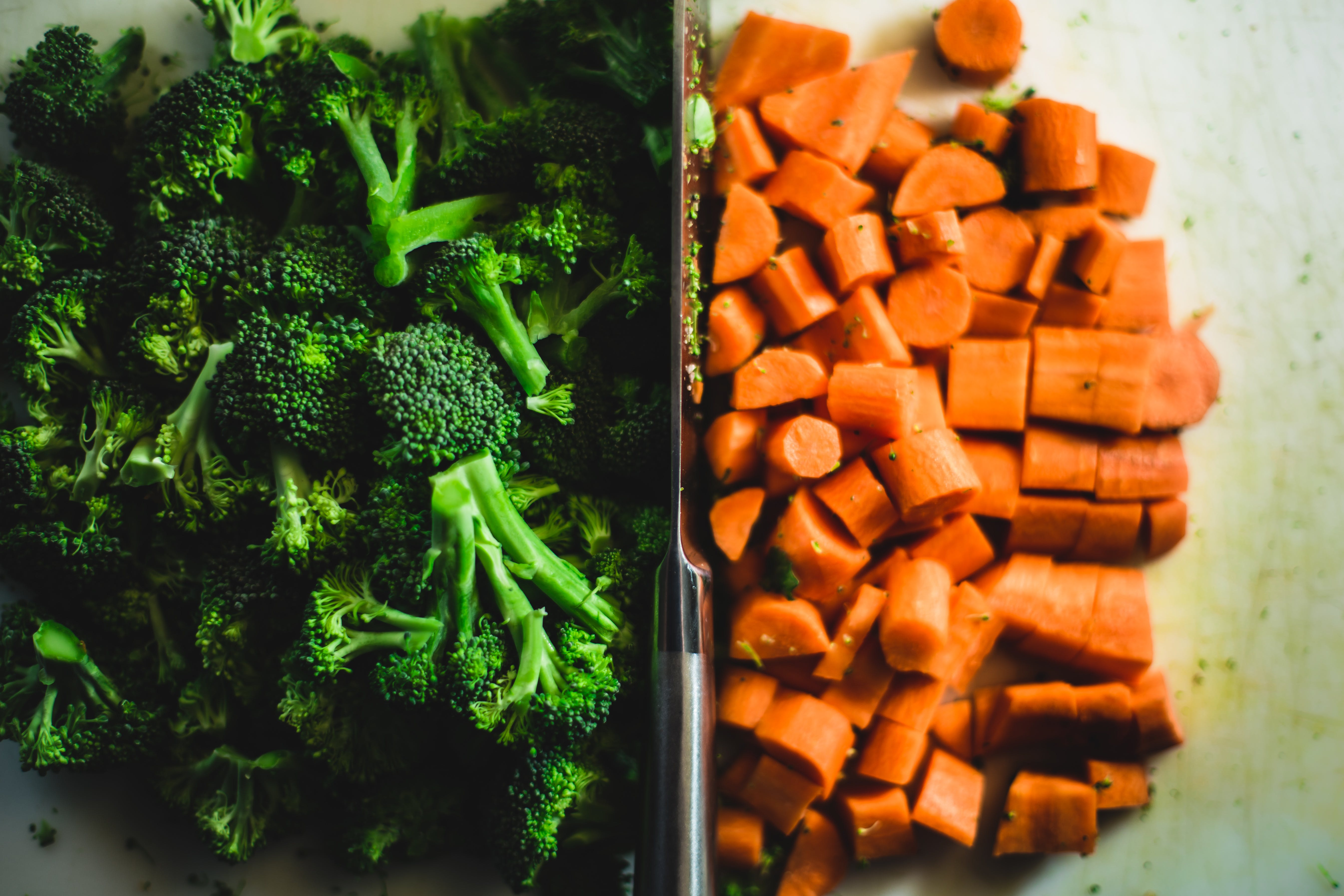 Gray Stainless Steel Knife Between Broccoli and Carrots in Close-up Photography