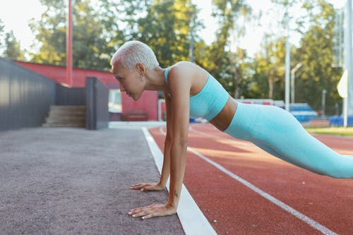 Woman in Blue Sports Bra and Blue Leggings Doing Push Ups