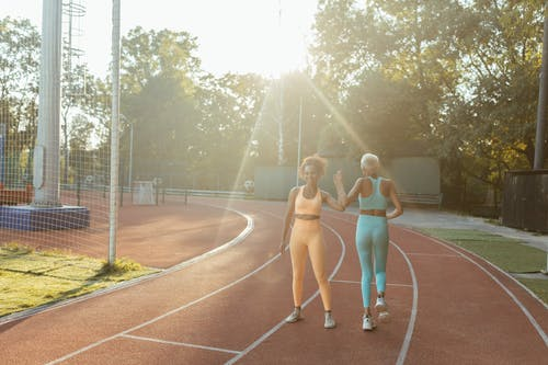 2 Women in White Sports Bra and Blue Shorts Running on Track Field