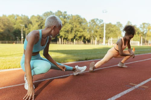 Women Stretching on the Sports Ground