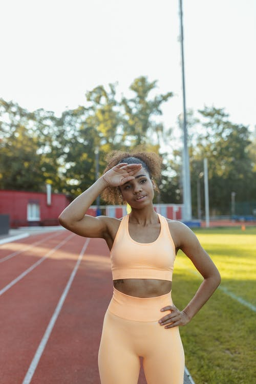 Woman in Yellow Sports Bra and White Panty Standing on Track Field