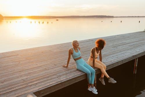 Women Sitting on a Wooden Jetty