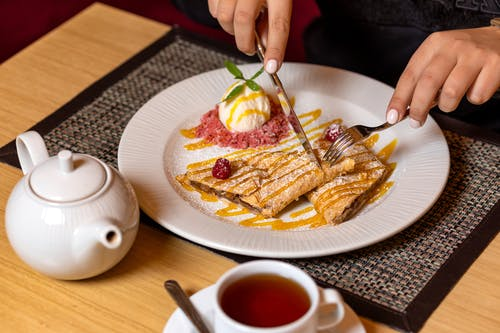 Hands with Fork and Knife Slicing Crepes on Round Plate