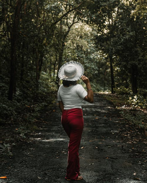 Woman in White Shirt and Red Pants Walking on Pathway Between Trees