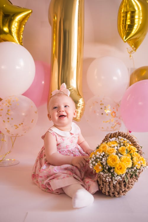 Baby Girl in Pink Dress Sitting on Floor with Basket of Flowers