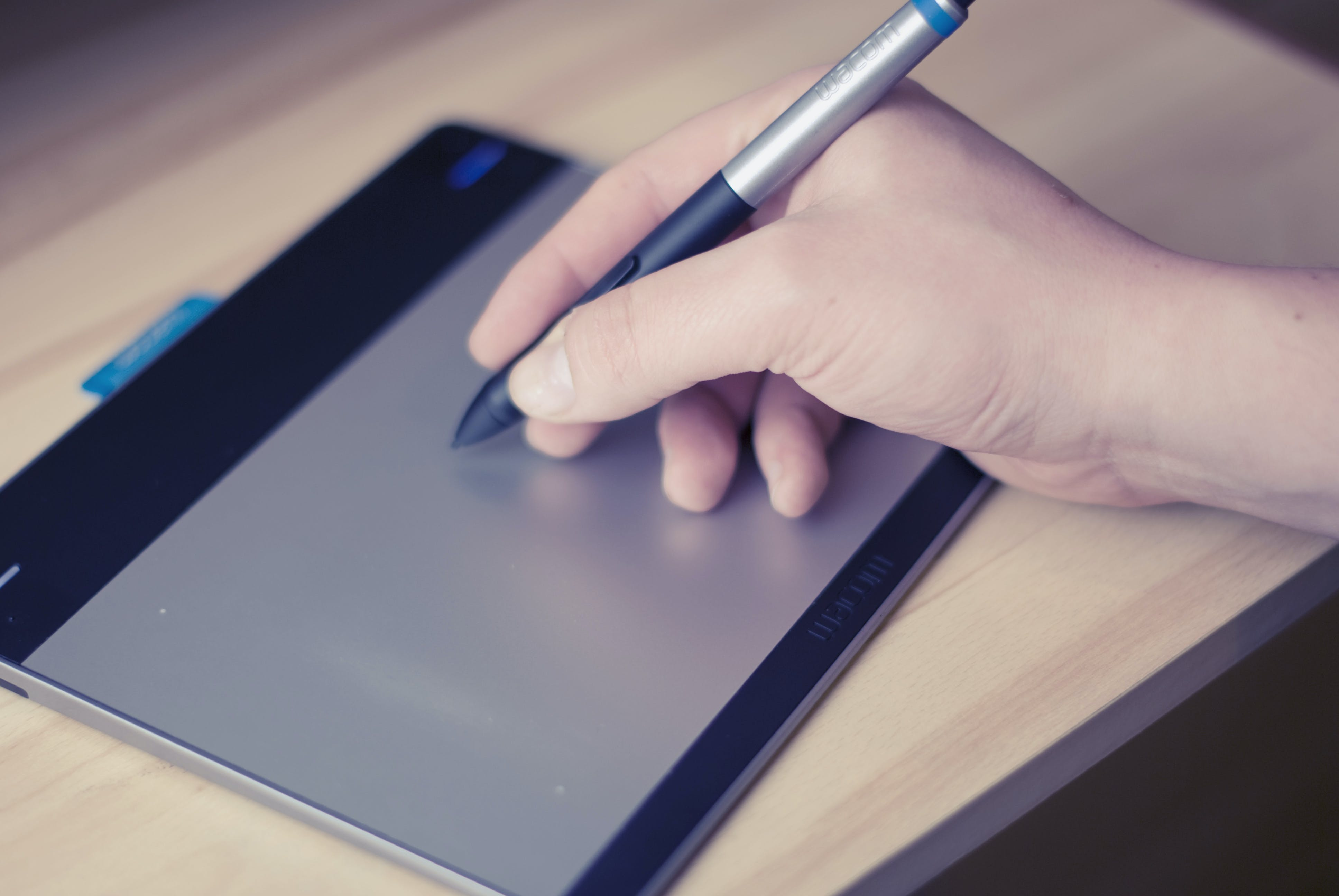 Person Holding Stylus Pen on Writing Pad