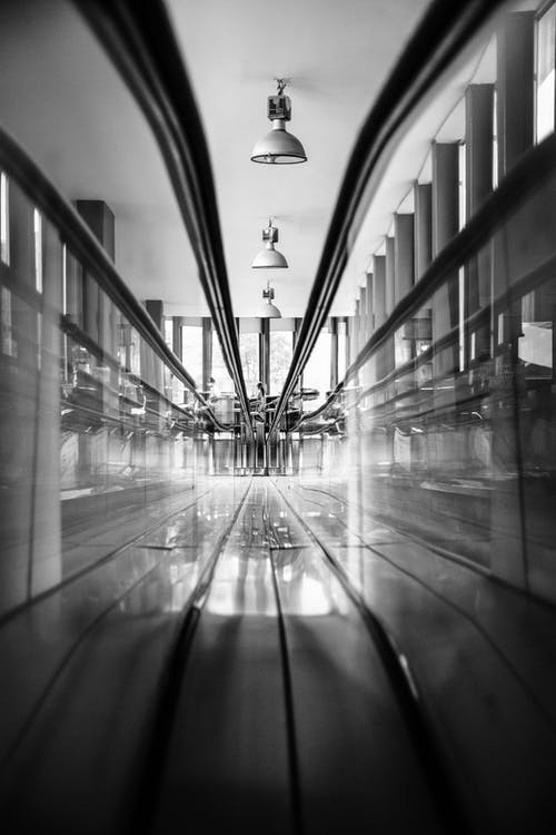 Grayscale Photo of Hallway With Glass Walls
