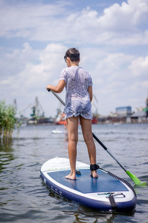 Woman in Grey Shirt and Red Shorts Standing on White and Green Surfboard