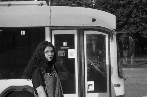 Woman in Black Coat Standing Beside White Train