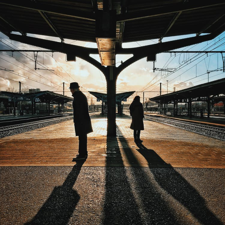Man and Woman Silhouette Standing on Brown Ground at Daytime