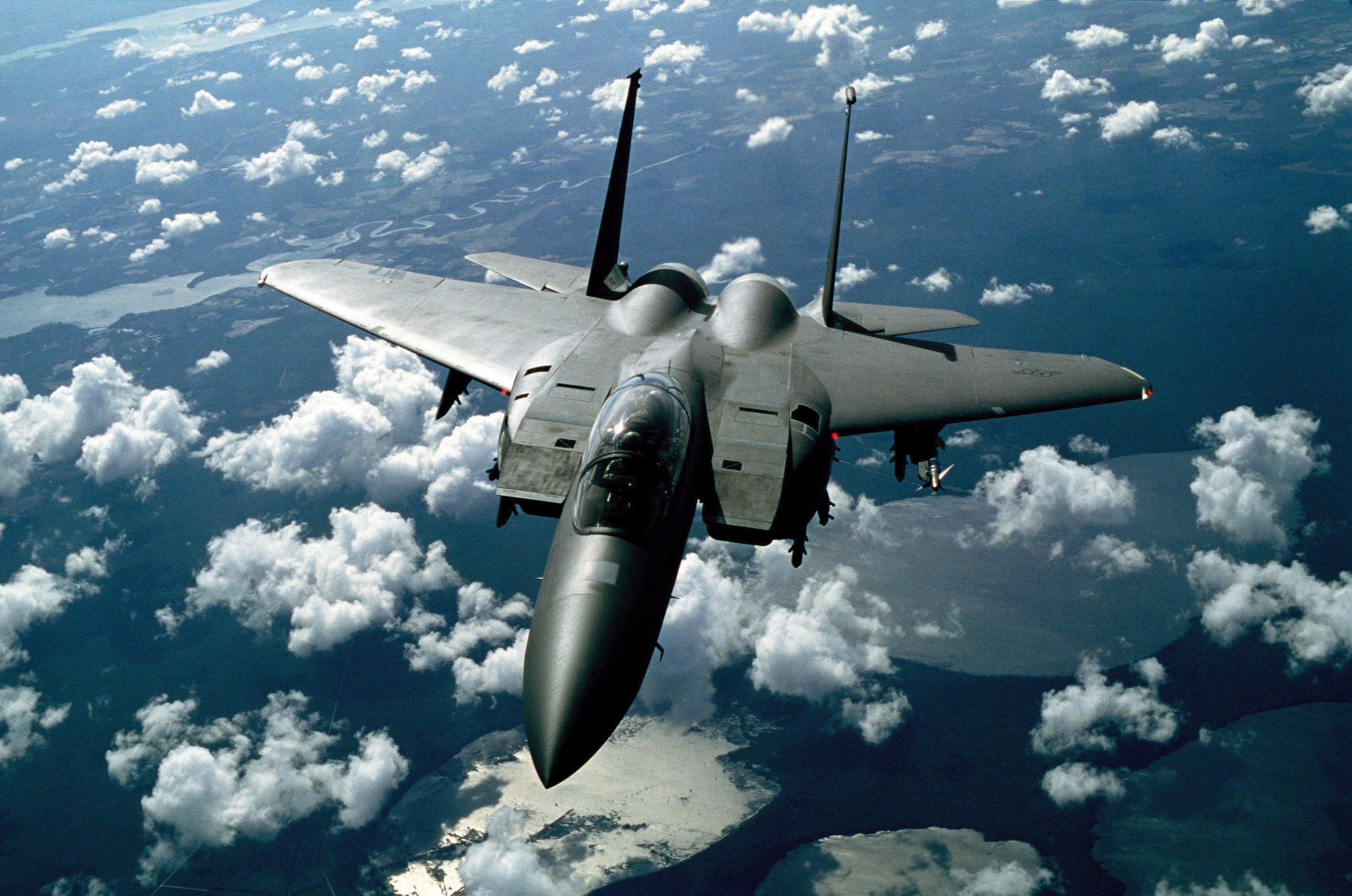 Gray Fighter Jet in White Clouds