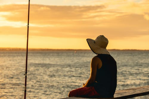 Woman in Black Tank Top and Brown Sun Hat Sitting on Beach during Sunset